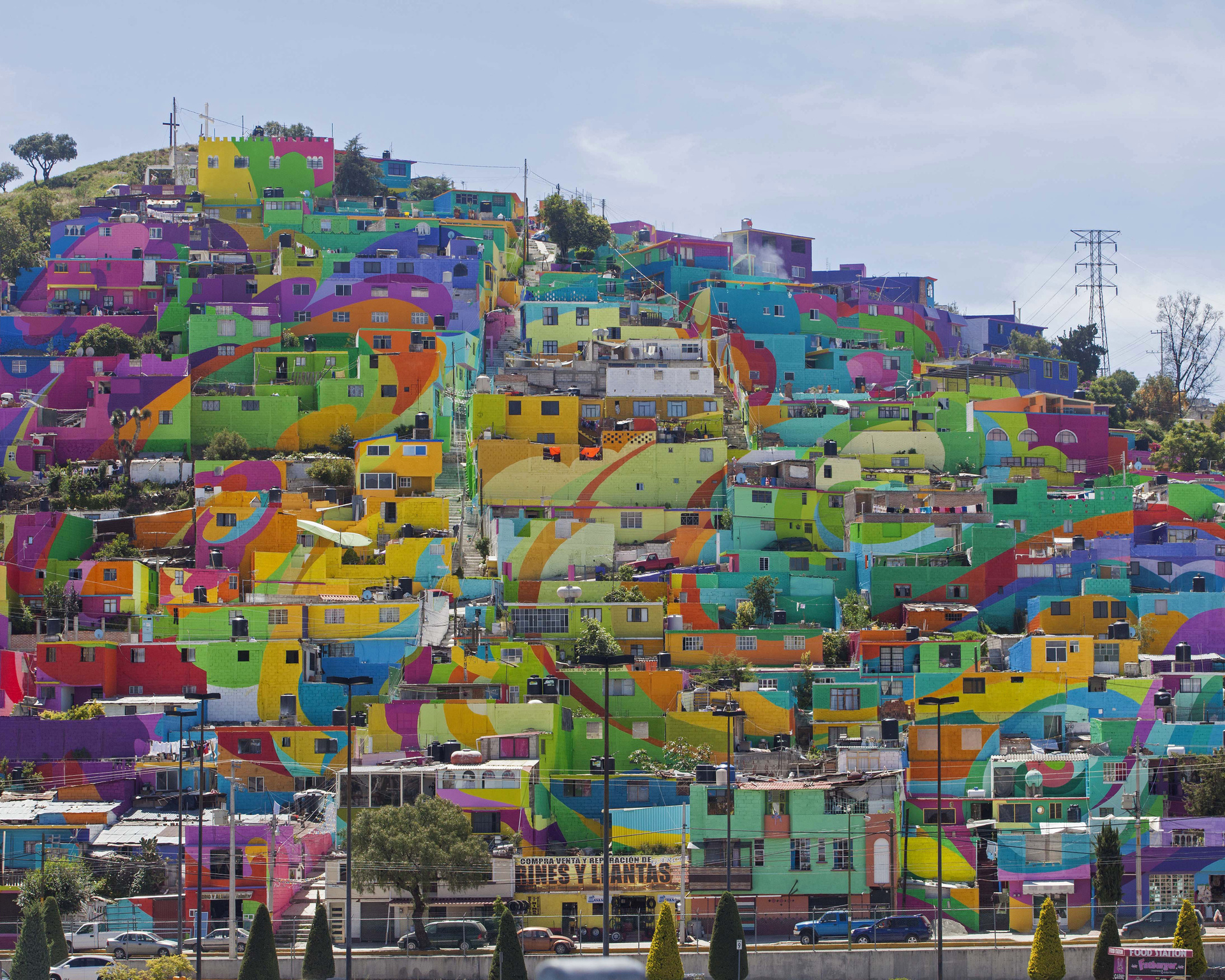 Hundreds of houses painted in bright colors in what organizers claim is Mexico's largest mural, is part of a government-sponsored project is called Pachuca Paints Itself, in the Palmitas neighborhood, in Pachuca, Mexico, Thursday, July 30, 2015. German Crew is the artist collective responsible for painting the mural project. Director Enrique Gomez, who goes by MYBE, said the crew has painted 1,500 square meters with 20,000 liters of paint. The project aims to bring the community together and rehabilitate the area. (AP Photo/Sofia Jaramillo)